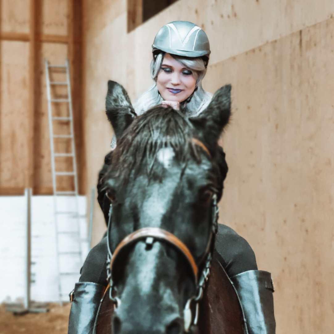 Kuvassa peruukkipäinen tyttö istuu hevosen selässä